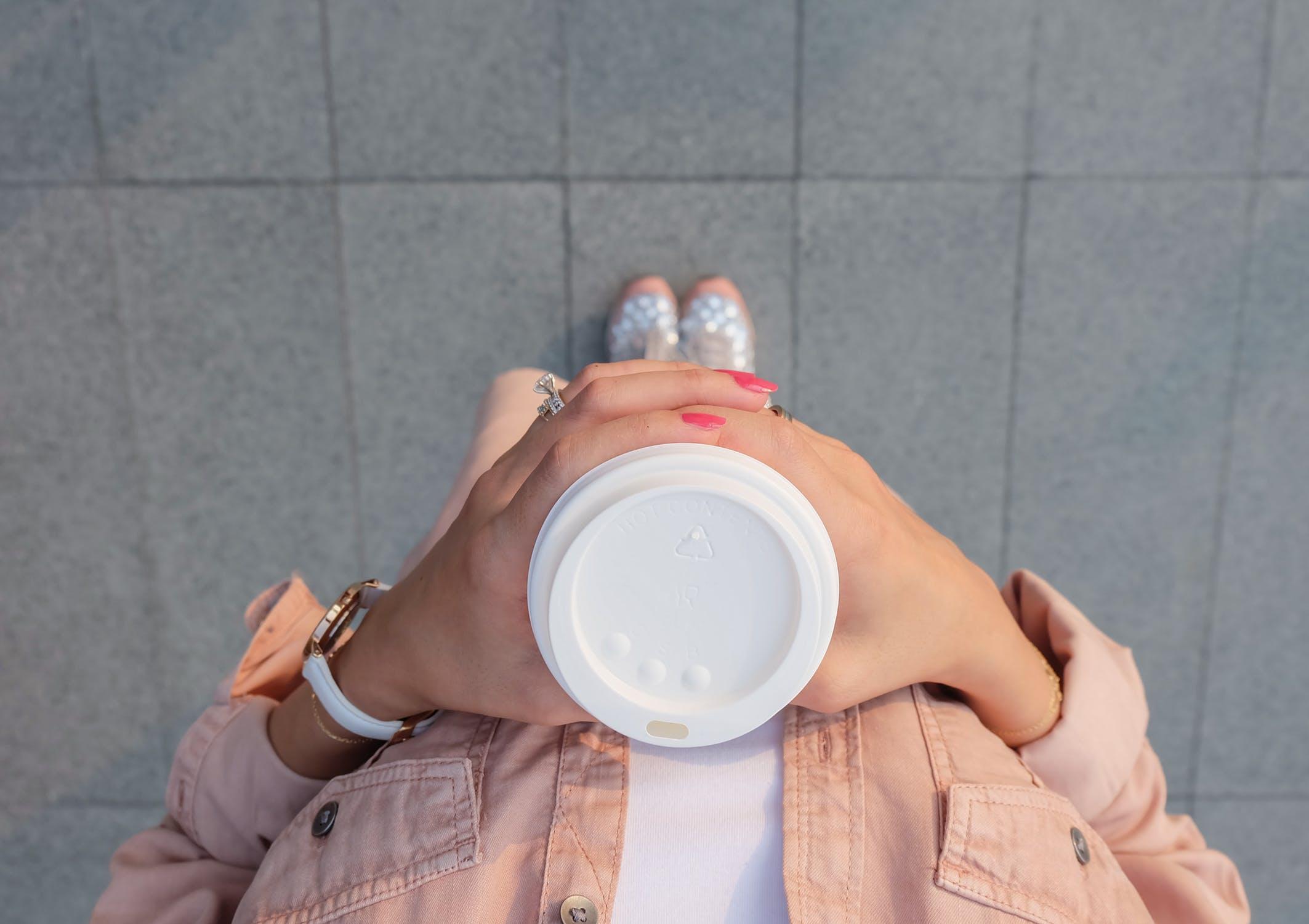 Kvinde, der holder kaffe til at tage med